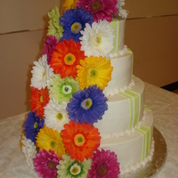 "Gerbera Wedding Cake  14"", 12"", 8"" and 6"" white almond with buttercream icing. Fondant stripes and silk flowers. I loved the all the color,..."
