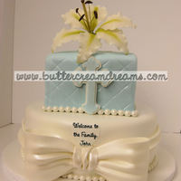 Baby's Baptism Cake Handmade gumpaste lily, cross, and bow adorn a 2-tiered cake.