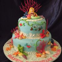 Mermaid Fondant covered cake with fondant corals. Mermaid is alsomade from fondant with added gumtex.