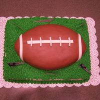 Superbowl Cake Superbowl cake made with the Wilton football pan sitting on a base of chocolate sheet cake. Football covered in chocolate MMF. Bottom base...