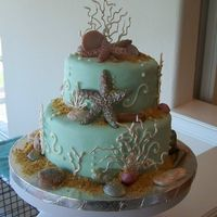 Beach Birthday Cake This was done for my husband's birthday. Two tier cake covered in fondant. Seashells are gumpaste; coral and piping on cake are royal...
