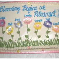 Retirement Cake For Seven Ladies Half white/half Chocolate cake iced in BC with MMF flowers.