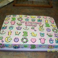 Baby Quilt Cake Cake is covered in pale pink and green buttercream. Baby designs are made of colorflow.