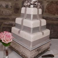 Wedding Cake Varied flavors per tier, fondant covered, gumpaste bow and bands.