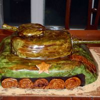 Army Tank Groom's Cake 12x18 Chocolate Chip cake carved with Satin Ice Fondant. Hand painted camo. Guns are made out of gumpaste. Thanks for looking!