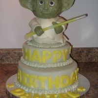 Yoda  Yoda cake made for a little boy turning 6... Cake is covered in mmf, with chocolate clay details. Yoda is made of rice krispie treats (form...