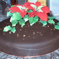 Christmas Poinsettia This is a strawberry cake covered with buttercream icing and chocolate Satin Ice, sprinkled with edible gold flakes and topped with...