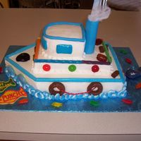 "Tugboat Cake This is iced in buttercream with candy accents. The smoke stack is a plastic dowel covered in fondant and the ""smoke"" is cotton...."