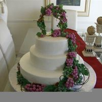 Grape And Wine Theme Wedding Cake 3 tier white fondant wedding cake with pink and green (white choc) grapes and leaves made from fruit roll ups... added vines and a arbour...