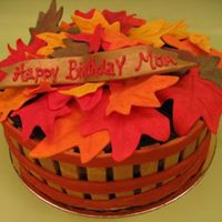 Autumn Birthday A wooden basket full of autumn leaves. Chocolate cake with peanut butter buttercream covered in chocolate ganache. All decorations are...