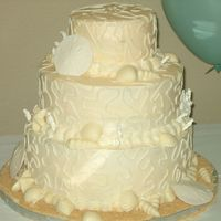 Beach-Theme Wedding Cake Buttercream icing. Sand dollars are made from gumpaste, shells are made from chocolate.