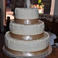 Buttercream Wedding Cake With Ivory Stringwork With Taupe Ribbon This was white cake with a layer of apricot jam pureed then a layer of white chocolate pudding on top of that for the filling. It was an...