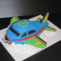 Airplane For Alec Carved from an 11X15 cake and football cake. Fondant covered foamboard for wings and tailpieces. Frosted in BC.