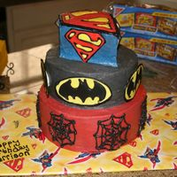 Super Hero Cake The emblems are colorflow.. my first attempt! The top tier is carved like Superman's emblem.. also my first carving!