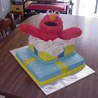 Elmo Cake   this is my elmo cake for a 1 year old boy. The elmo is made of rice krispies and covered with butter cream. Enjoy