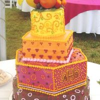 Colorful Dots Wedding Cake Warm colors and Dots in a variety of designs. All butter cream icing. The cake topper is artificial fruit to compliment the warm, bright...