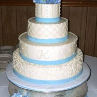 White With Blue Ribbon White buttercream with blue fondant ribbon featuring a variety of patterns on each tier, including a monogram. Silk hydrangeas on top and...