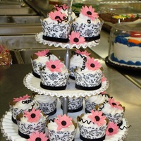Black & White Cupcake Wraps With Pink Daisies Cupcake wraps are made from scrapbook paper and black velvet ribbon was added for border. Daisies are pink fondant with black fondant vines...