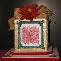 Christmas Present Cake With Poinsetta And Bow This was my OSSAS entry. Poinsetta was hand drawn w/#2 tip and veining was done with #00. Bow is gumpaste. Border is a long line of the...
