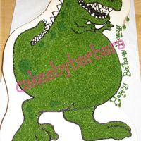Friendly Dino 1/2 sheet cake shaped into friendly dino to match invitation. iced in buttercream.