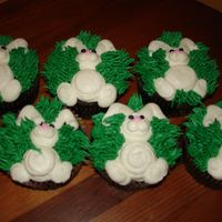 Bunnies cupcakes with little bunnies laying in the grass. All buttercream.