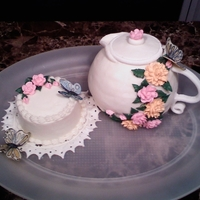 Tea Time Teapot covered with MMF decorated with royal icing flowers - MMF doily and mini cake decorated with buttercream and royal icing flowers....