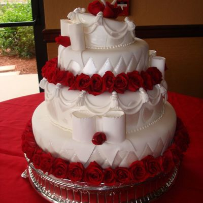 Topsy Turvy Wedding Cake Decorated With Hearts And Red Roses