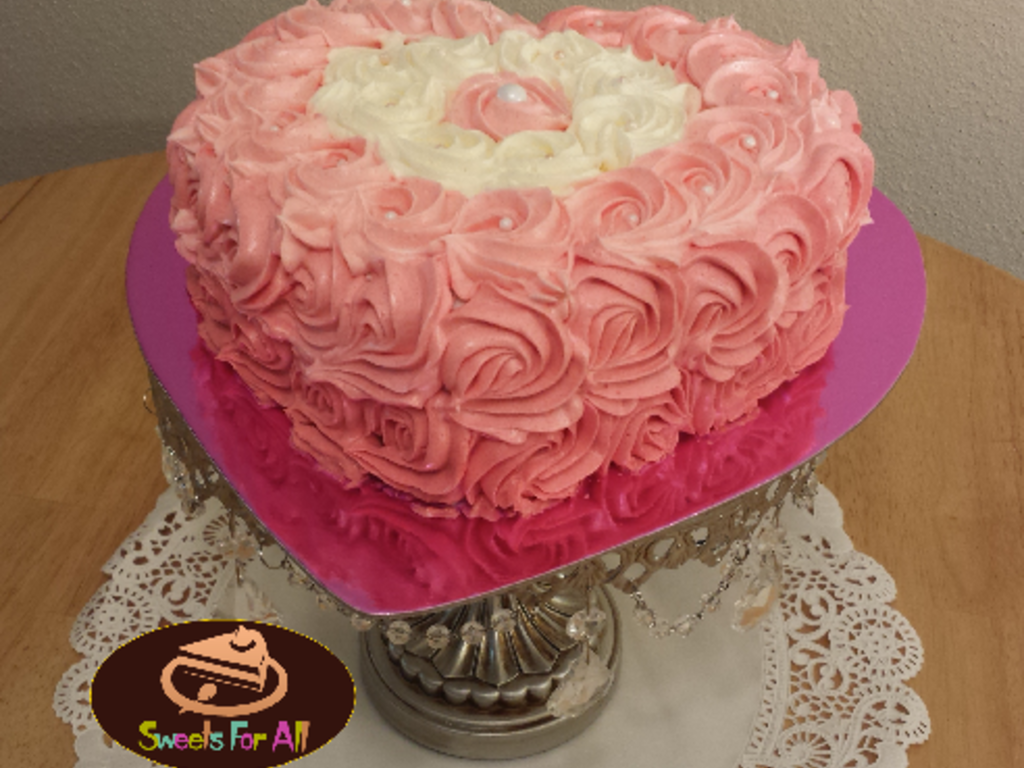 A Heart Shaped Cake Decorated With Buttercream Roses In Amber Pink ...