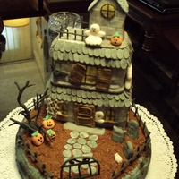 Spooky Mansion  1 tier cake covered with gray buttercream and a spooky cake mansion covered in fondant in a graveyard with gumpaste ghosts, bats and...