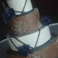 Chocolate And Purple Wedding Cake   Brown and White buttercream cake with purple fantasy flowers.