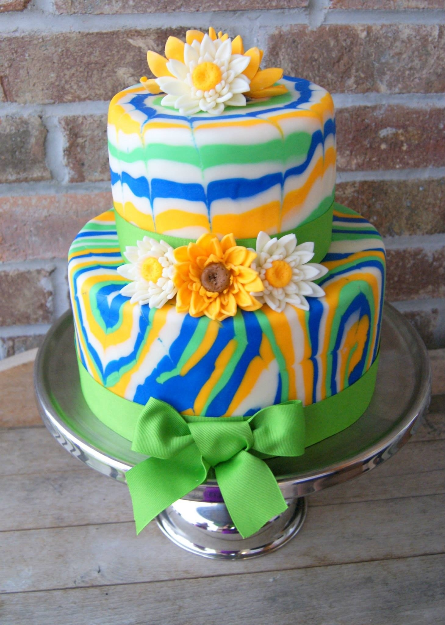 Tie-Dyed Wedding Cake Tie-dyed fondant with daisies and brown eyed Susan's.