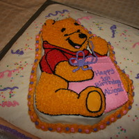 Pooh Present  Square vanilla cake covered in buttercream topped with a chocolate Winnie the Pooh cake also covered in buttercream, giving a present for a...
