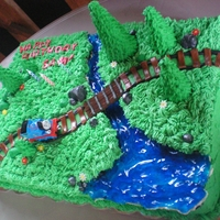 Thomas The Tank Engine Cake For my younger son's 3rd birthday. Grass is buttercream. Trees are ice cream cones with royal. Rocks, flowers, tracks are fondant. (...