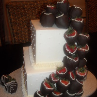 Cascading Strawberry buttercream cake with chocolate cover strawberries cascading down it