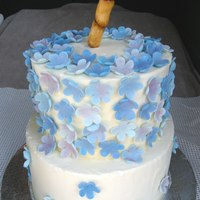 Bamboo And Flowers Vanilla cake with raspberry mousse filling, iced in vanilla buttercream and decorated with gumpaste flowers in shades of blue and dusted...