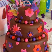 Jasmin's First Birthday Cake Brown Pink Purple Orange Flowers Butterflies Three tier cake covered in chocolate fondant with pink, orange and purple fondant accents. Thanks for looking.