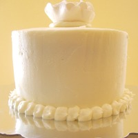 White Bridal Shower  Small plain white bridal shower cake with a white gumpaste flower on top. The topper was the monogram taken from the invitation and was...