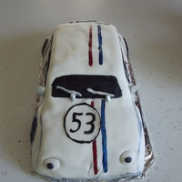 Herbie White cake covered in fondant and decorated. THe colors on the car are hand painted with cake color. I made mirrors and windshield wipers...
