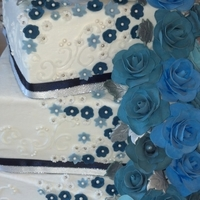 Blue Flowers Iced in buttercream with piped scrolls. Flowers are made with gumpaste. This was my first attempt at making gumpaste roses.