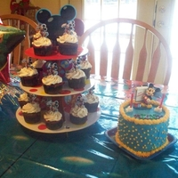 "Mickey Mouse 2Nd Birthday A cupcake stand with cupcakes and a 6"" round double layer with buttercream frosting"