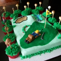Funny Golfer Sheet cake with golfer trying to blow the ball in the hole, with cupcake spectators-heads made of fondant on real golf tee's