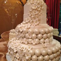 Cake Ball Wedding Cake With Satellite Cakes  Three tier wedding cake covered in fondant. White chocolate cake balls cover the middle and bottom tiers. Cascading hydrangea blooms made...