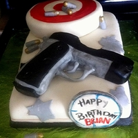 Gun Birthday Cake! A raspberry filled vanilla cake, (gun and target also cake.) Covered in white chocolate BC, and MMF. Bullets are MMF with shimmer powder on...