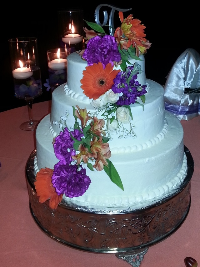 Three Tier With Fresh Flowers This is a three tier cake with buttercream frosting. Bride wanted fresh flowers in purple and coral.