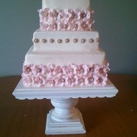 Medallion Cake 2 1/2 tier wedding cake. 5 petal flower with bronzed medallions. Pearls in centers.
