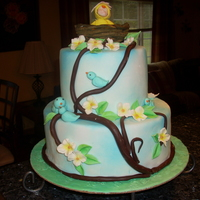 'baby Chick In Nest Baby shower cake with candy clay tree limbs, gumpaste baby in a baby chick costume.