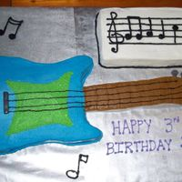 "Blue Guitar Vanilla cake with buttercream icing. MMF bridge/pegs/knobs. The music sheet has the first 6 notes from ""Happy BIrthday"" song...."