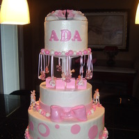 Baby Ada Cake White cake covered in buttercream, fondant accents, and plastic babies