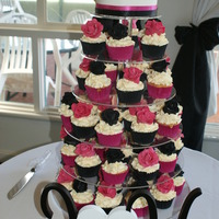 Wedding Cupcake Tower This is a choc cake on top with 60 vanilla cupcakes and each had a hand made rose.