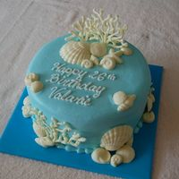 Ocean Theme Birthday Cake   Simple round cake decorated with white chocolate molded shells and coral.